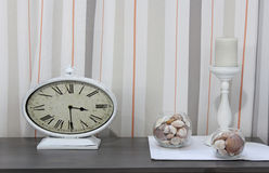Vintage clocks, vases with shells and candle on the shelf Royalty Free Stock Photos