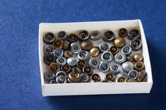 Vintage clockwork parts in paper box. Blue background, macro shallow depth of field Royalty Free Stock Photo