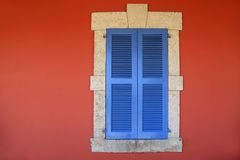 Window with blue shutters in old red stucco house. Vintage close window with blue shutters in old red stucco house royalty free stock photo