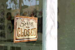 Vintage closed sign. Hanging in front of shop window Stock Photos