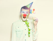 Vintage Clown With Birthday Balloons And Streamers. Laughing Retro Clown Holding Celebration Balloons And Streamers While Celebrating A Happy Birthday Royalty Free Stock Photography