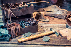 Vintage cobbler workplace with shoes, laces and tools Stock Photo