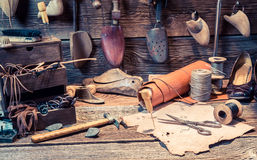 Vintage cobbler workplace with tools, leather and shoes Stock Photography