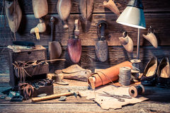 Vintage cobbler workplace with tools, shoes and laces Stock Image
