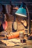 Vintage cobbler workshop with shoes, laces and tools Stock Photography