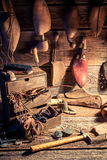 Vintage cobbler workshop with tools, leather and shoes Royalty Free Stock Images