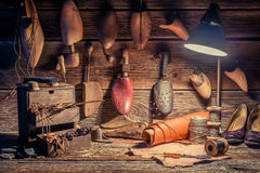 Vintage cobbler workshop with tools, shoes and laces Royalty Free Stock Images