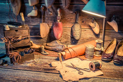 Vintage cobbler workshop with tools, shoes and leather Stock Images