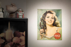 Vintage CocaCola poster. Ketchikan, Alaska, USA - July 21th, 2017: A Viintage poster of Coca Cola with a young woman holding a little bottle of Coke smiling Stock Images