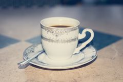 Vintage coffee cup with hot coffee. On a cafe table with spoon. Espresso coffee Stock Photography