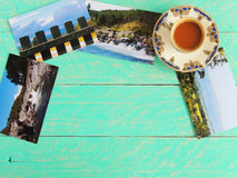 Vintage coffee cup and postcards, on a painted wood background Stock Photos