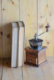 Vintage coffee grinder and books. On wooden background Stock Photography