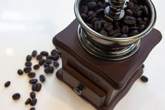 Vintage coffee grinder with coffee beans. Vintage manual coffee grinder with coffee beans isolated on white background Royalty Free Stock Photo