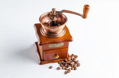 Old coffee grinder with coffee beans on white table. stock images