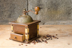 Vintage coffee grinder on rustic background. Vintage coffee grinder and coffee beans on a old wooden table and a rustic background Royalty Free Stock Photos