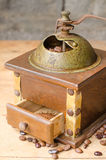 Vintage coffee grinder on rustic background. Vintage coffee grinder and coffee beans on a old wooden table and a rustic background Stock Photography
