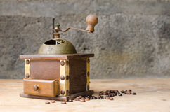 Vintage coffee grinder on rustic background. Vintage coffee grinder and coffee beans on a old wooden table and a rustic background Royalty Free Stock Photography