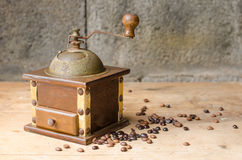 Vintage coffee grinder on rustic background. Vintage coffee grinder and coffee beans on a old wooden table and a rustic background Stock Images
