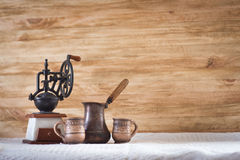 Vintage coffee grinder turkish and cup. At wooden background Stock Photo