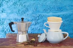Vintage coffee makers. Arrangement of vintage coffee makers, on an old desk against a blue plastered wall royalty free stock photography