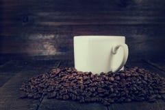 Vintage coffee mug with grains on dark wood background Royalty Free Stock Image