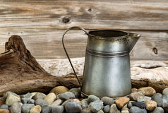 Vintage coffee pot on stone fire pit with driftwood in backgroun Royalty Free Stock Images