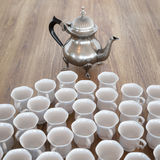 Vintage Coffee Pot On Wooden Surface With Many White Cups Stock Photos