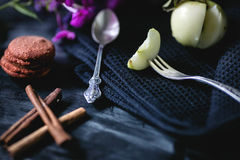 Vintage coffee spoon and fruit fork. Cinnamon, coffee and macaroni on the old table. Vintage coffee spoon and fruit fork close up. Cinnamon, coffee and macaroni Royalty Free Stock Photography