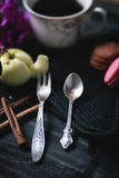 Vintage coffee spoon and fruit fork. Cinnamon, coffee and macaroni on the old table. Royalty Free Stock Photography