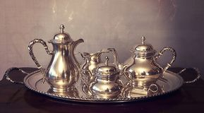 Vintage coffee and tea set on tray. Vintage silver coffee and tea set composed by coffee pot,teapot, creamer and sugar bowl on oval tray in San Marco classical Stock Image