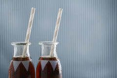 Vintage cola drink bottles with straws and copy space. On a grungy blue striped background Royalty Free Stock Photography