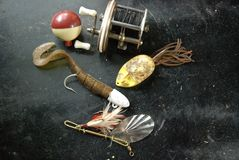 Vintage collection of fishing gear. Vintage collection of fishing lures, fishing bobber and fishing reel on a black surfaced work table Stock Photography