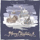 Vintage color Christmas card with mountain village and holiday brush lettering on blue background Stock Images