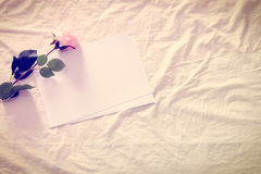 Vintage color style effect : Blank / empty papers with artificial pink rose on a crumpled bed sheet. Stock Photo