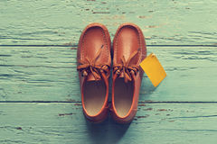 Vintage color style, Male shoes with tag on wooden background. Fashion concept Stock Photos