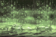 Vintage  color tone of close up rain water drop falling to the f Stock Photos