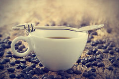 Vintage color tone, coffee cup with spoon and beans on the old wooden background Stock Photo
