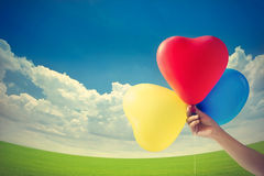 Vintage color tone style, balloon heart shape on the grass field Royalty Free Stock Photos