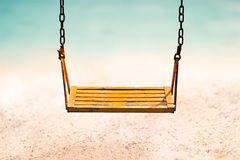 Vintage color tone style of yellow swing on sand sea beach summer day Stock Photography