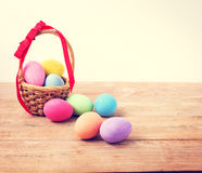 Vintage colorful Easter eggs in basket on wood. Table background Stock Photo