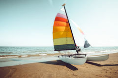 Vintage colorful sailboat on tropical beach in summer. Stock Photos