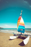 Vintage colorful sailboat on tropical beach in summer Stock Photography