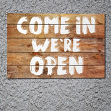 Vintage Come in we are open wooden sign on stucco concrete wall. Royalty Free Stock Image