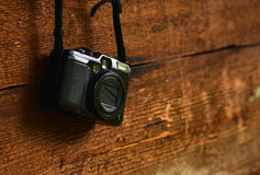 Vintage compact photo camera hanging on a wooden wall Royalty Free Stock Image