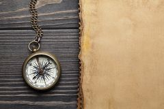 Vintage compass and blank paper sheet on wooden table stock photography
