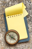 Vintage compass and blank yellow notepad Royalty Free Stock Images