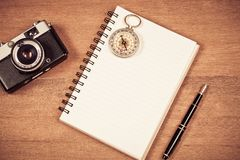 Vintage compass on book note and fountain pen. On wood table stock image