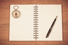 Vintage compass on book note and fountain pen. On wood table royalty free stock photo