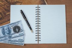 Vintage compass on book note and fountain pen. On wood table stock photos