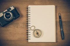 Vintage compass on book note and fountain pen. On wood table stock photo